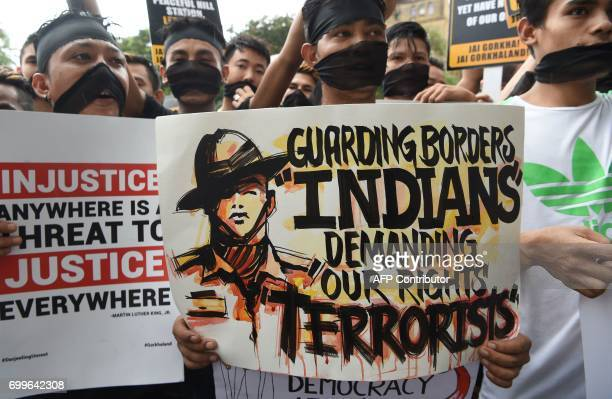 Indian supporters of the Gorkha Janamukti Morcha wearing a black cloth tied on their face as a mark of protest listen to their leader during a...