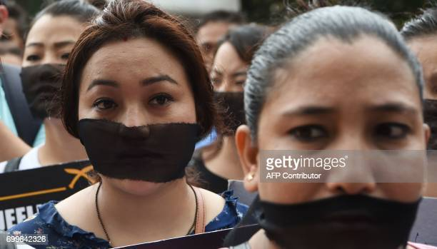 Indian supporters of the Gorkha Janamukti Morcha wearing a black cloth tied on their face listen to their leader during a protest rally in support of...