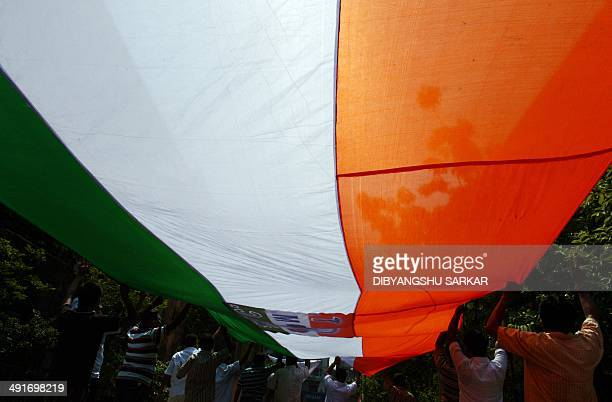 Indian supporters of the Trinamool Congress carry a flag as they celebrate the party's election results and greet supporters in Kolkata on May 17...