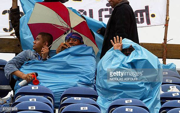 Indian supporters shelter under umbrellas and plastic bags at the VRA Cricket Ground in Amstelveen south of Amsterdam 23 August 2004 Australia plays...
