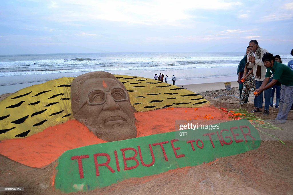 Indian supporters toss flower petals on a sand sculpture of chief of the Hindu nationalist Shiv Sena party, Bal Thackeray created by sand artist Sudersan Pattnaik at Golden Sea beach in Puri, about 65 kilometers from Bhubaneswar on November 18, 2012. The final journey of Shiv Sena patriarch Bal Thackeray began with his body being taken out for the funeral procession from his residence in suburban Bandra Mumbai this morning amid the presence of thousands of grief-stricken Shiv Sainiks, who have come from across Maharashtra.