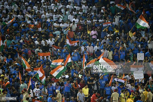 Indian supporters wave flags as they cheer ahead of the start of the World T20 cricket tournament match between India and Australia at The Punjab...