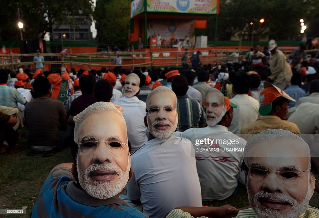 Indian supporters wearing masks bearing the image of Chief Minister of the western Indian state of Gujarat and India's main opposition Bharatiya Janata Party (BJP) prime ministerial candidate Narendra Modi wait to listen to him speak during a campaign rally in Kolkata on May 7, 2014. India's 814-million-strong electorate is voting in the world's biggest election which is set to sweep the Hindu nationalist opposition to power at a time of low growth, anger about corruption and warnings about religious unrest. AFP PHOTO / Dibyangshu Sarkar