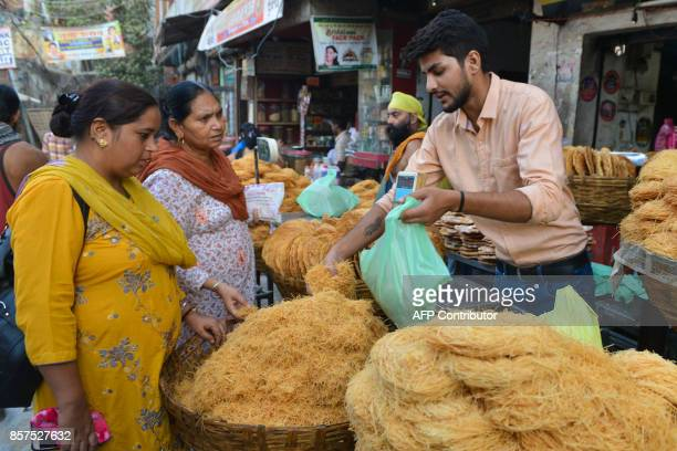 Indian sweet confectionary makers sell vermicelli to the customers outside of a sweet shop in Amritsar on October 4 2017 Traditionally sweets are...