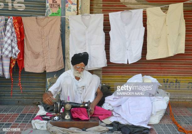 Indian tailor Kirpal Singh uses a sewing machine to stitch 'Fatuhi' a cotton cloth waistcoat which are traditionally worn under a shirt to conceal...