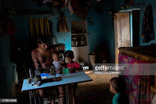 Indian tailor Sunil Kumar holds his neighbour's son as he talks to his sons Ayuz and Mohin while working at their home which doubles as his workshop...