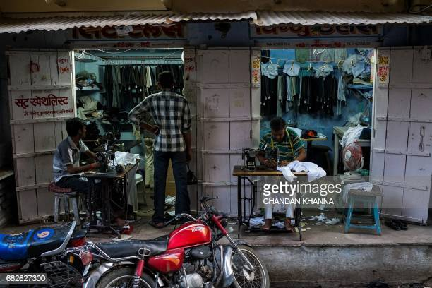 Indian tailors work sitting outside their shop in Kekri some 78 kms south of Ajmer on May 13 in the northern state of Rajasthan / AFP PHOTO / CHANDAN...