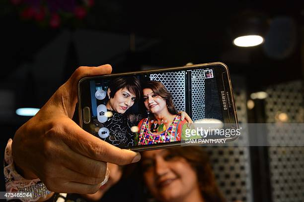 Indian tattoo artist Jagruti Parmar takes a selfie photo with her mobile phone after painting a picture of India's Prime Minister Narendra Modi...