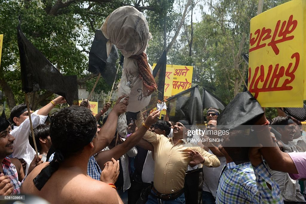Indian taxi drivers and owners burn an effigy of Delhi's Chief Minister Arvind Kejriwal during a protest in New Delhi on May 4, 2016, against the banning of diesel cabs on the roads in the Indian capital. Hundreds of taxi drivers and owners took to the streets of New Delhi to protest a court order banning diesel cabs from plying the roads of the world's most polluted capital. The ban would impact some 27,000 diesel taxis registered in Delhi, including app-based cab operators Ola and Uber. / AFP / PRAKASH
