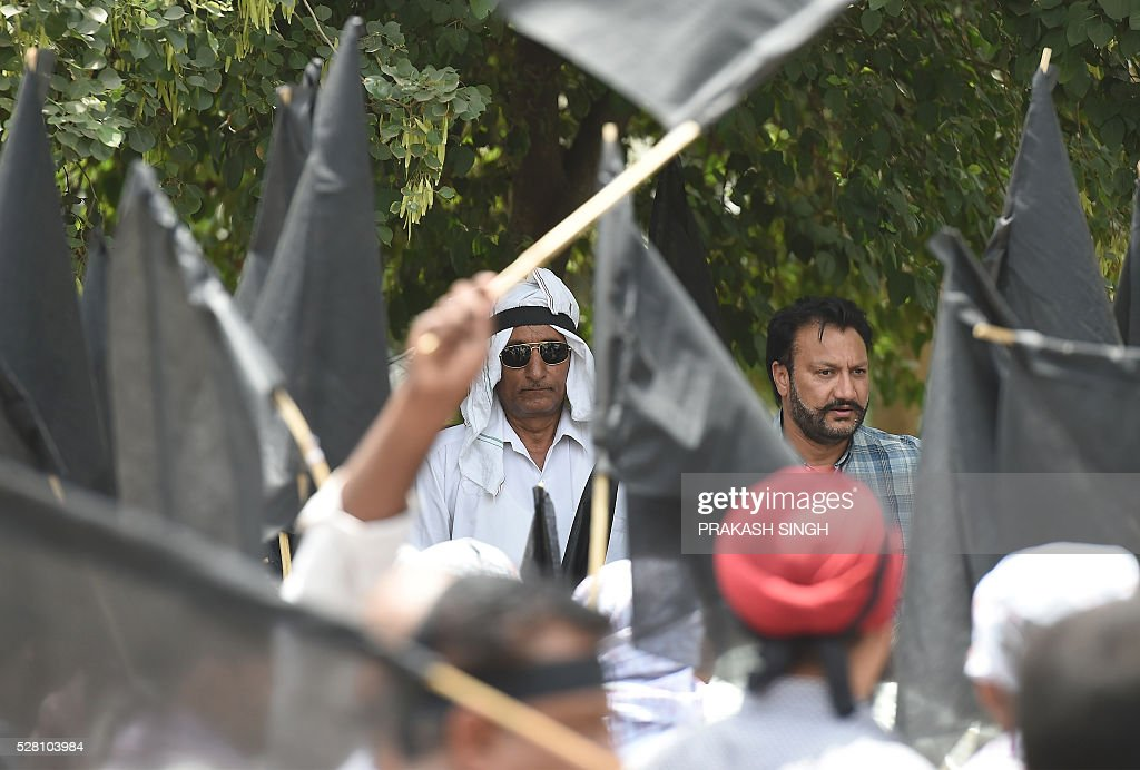 Indian taxi drivers and owners hold black flags as they listen to their leaders speak during a protest in New Delhi on May 4, 2016, against the banning of diesel cabs from the roads in the Indian capital. Hundreds of taxi drivers and owners took to the streets of New Delhi to protest a court order banning diesel cabs from plying the roads of the world's most polluted capital. The ban would impact some 27,000 diesel taxis registered in Delhi, including app-based cab operators Ola and Uber. / AFP / Prakash SINGH