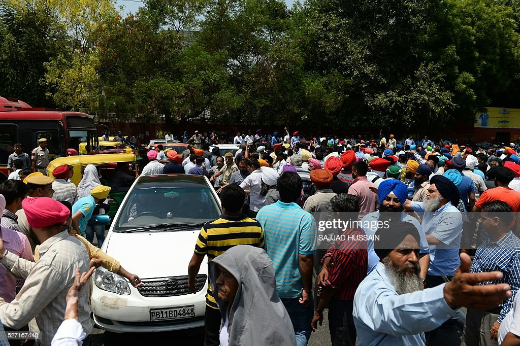 Indian taxi drivers and owners shout slogans as they block a road during a protest in New Delhi on May 2, 2016, against the banning of diesel cabs from plying the roads of the Indian capital. Hundreds of taxi drivers took to the streets of New Delhi to protest a court order banning diesel cabs from plying the roads of the world's most polluted capital. / AFP / SAJJAD