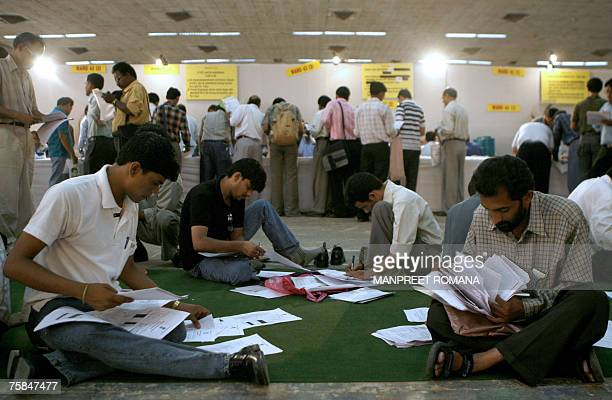 Indian taxpayers fill in their income tax returns at a special income tax filing facility at Pragati Maidan in New Delhi 29 July 2007 There is a last...