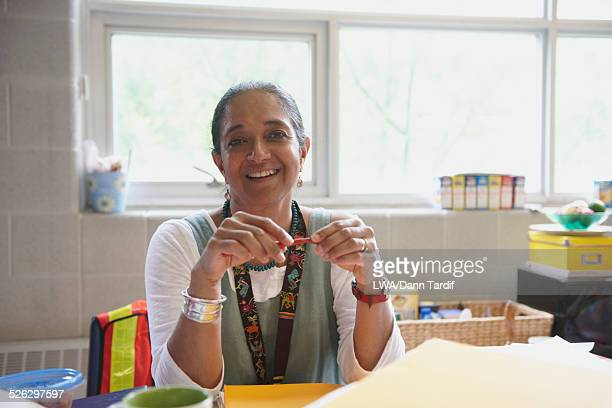 Indian teacher smiling at desk in classroom