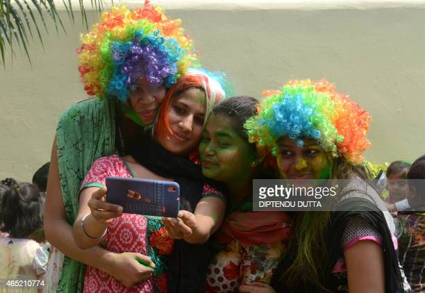 Indian teachers from the Bright Academy take a 'selfie' photograph after playing with colored powder known as gulal as they celebrate the Holi...