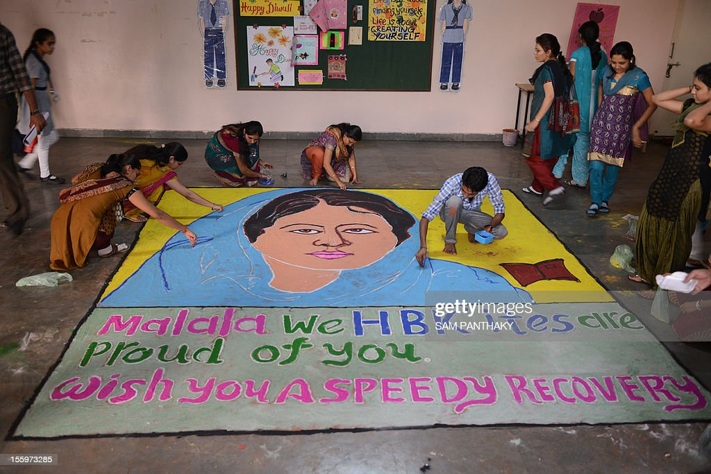 Indian teachers give the finishing touches to a 'Malala Rangoli' at H B Kapadia New High School in Ahmedabad on November 10, 2012. World Malala Day is being observed today to honour Pakistani child activist Malala Yousafzai who was shot by Taliban gunmen. In his message, UN Secretary General Ban Ki-moon has called on the international community to join the UN campaign to put education first for Malala and girls and boys throughout the world. AFP PHOTO / Sam PANTHAKY