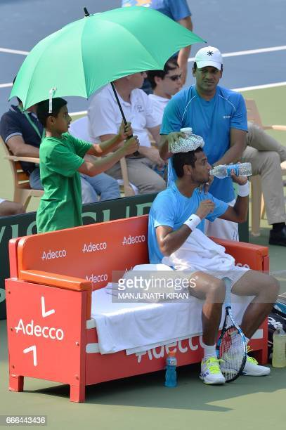 Indian team nonplaying coach Mahesh Bhupathi helps player Ramkumar Ramanathan cool off during a break in his singles match against Uzbekistan's...