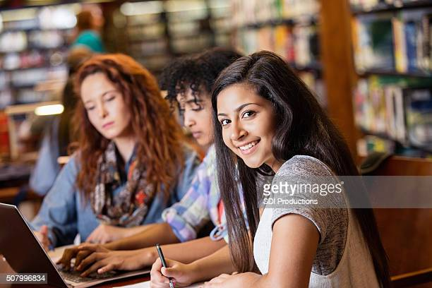 Indian teen studying in library with college age friends