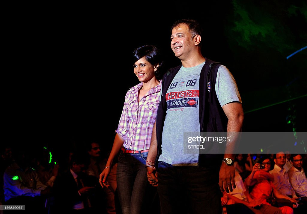 Indian television actress and anchor Mandira Bedi with husband Raj Kaushal walk the ramp during a Future Lifestyle Fashion event in Mumbai on November 21, 2012. AFP PHOTO/STR