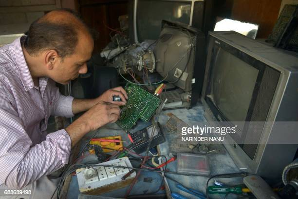 Indian television repairman Balwinder Pal works at his shop in Amritsar on May 26 2017 Pal said he earns around 300600 INR a day for his electronics...
