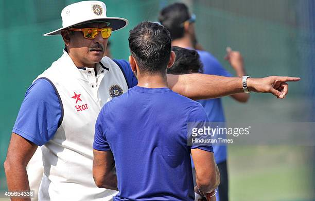 Indian Test team skipper Virat Kohli interacts with Team Manager Ravi Shastri during the net practice before India's scheduled match against South...