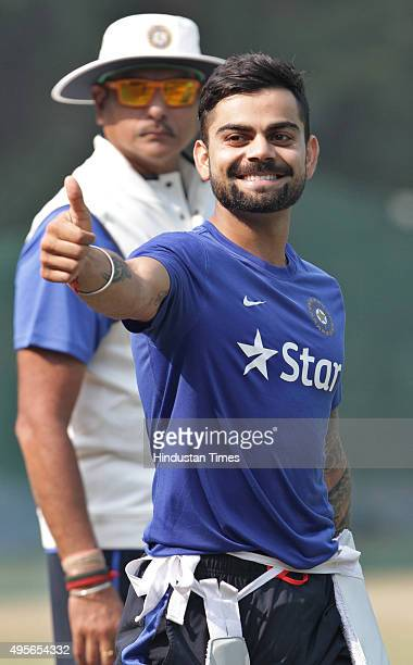 Indian Test team skipper Virat Kohli waves towards fans as Team Manager Ravi Shastri looks on during the net practice before India's scheduled match...