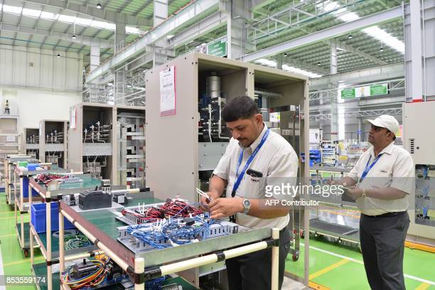 Indian Toshiba MitsubishiElectric Industrial Systems Corporation workers conduct product checks in the assembly area of the power electronics factory...