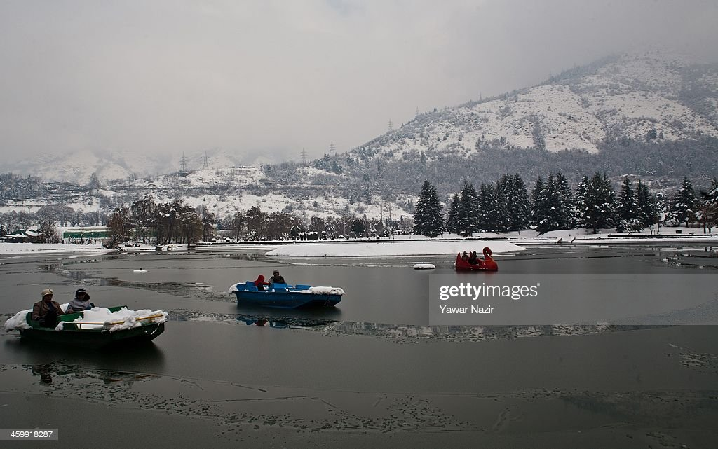 Indian tourist couples take joy ride in an ice covered pond after snowfall on January 01, 2014 in Srinagar, the summer capital of Indian Administered Kashmir, India. Weather conditions have improved in Kashmir after a spell of heavy snowfall that had distrupted road and air traffic, cutting off the Valley from the rest of world .