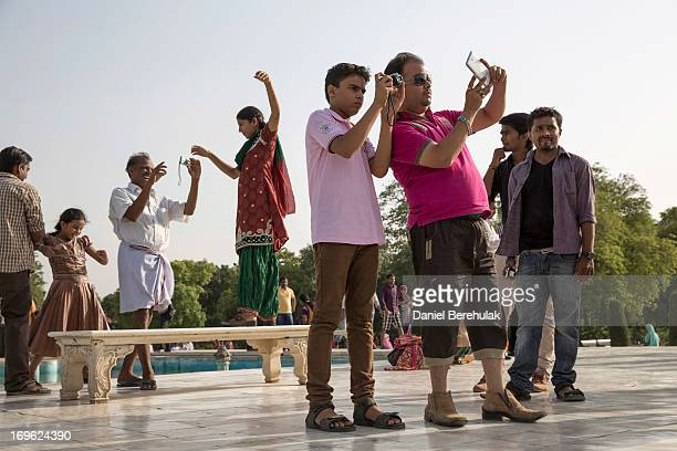 Indian tourists pose for photographs at the Taj Mahal on May 29 2013 in Agra India Completed in 1643 the mausoleum was built by the Mughal emperor...