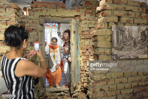 Indian tourists pose for photos as they stand by a faux demolished wall recreating postPartition violence debris during the reinauguration ceremony...