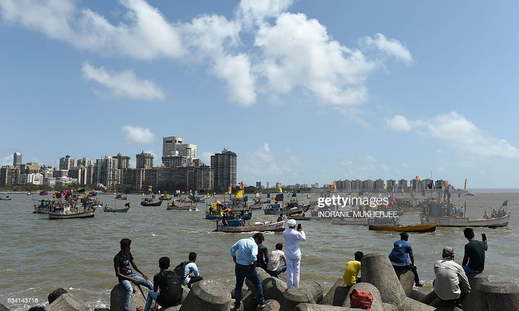 Indian tourists take photographs as fishing boats and crews take part in a 'Sea-Rally' to protest against the construction of The Chhatrapati Shivaji Memorial in the Arabian Sea off the coast of Mumbai on May 25, 2016. Some 100 fishing boats and fishermen participated in this rally to highlight the conditions which are going to arise after the construction of the proposed sea memorial for the legendary warrior Shivaji which may cause adverse effects to the livelihood of fishermen. / AFP / INDRANIL
