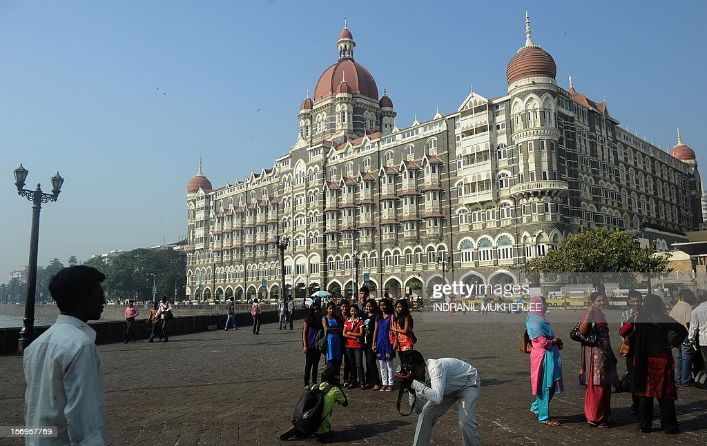 Indian tourists take photographs outside the iconic Taj Mahal Palace and Hotel - one of the sites of the 2008 terror attacks in Mumbai on November 26, 2012. A total of 166 people were killed and more than 300 others were injured when 10 heavily-armed Islamist militants stormed the city on November 26, 2008, attacking a number of sites, including the city's main railway station, two luxury hotels, a popular tourist restaurant and a Jewish centre.