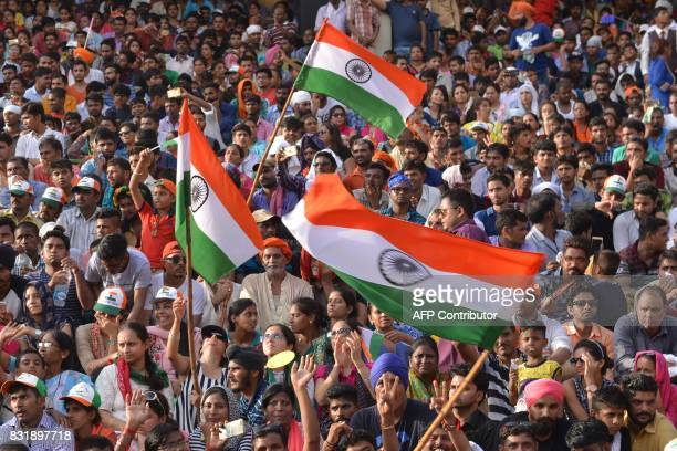 Indian tourists wave Indian flag during the daily beating of the retreat ceremony at the IndiaPakistan Wagah Border Post some 35kms west of Amritsar...