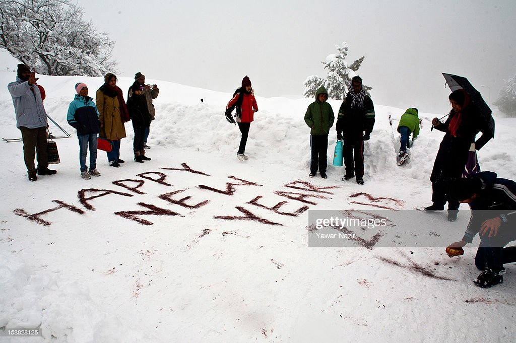 Indian tourists write a New Year's greeting into the snow on December 31, 2012 in Gulmarg, to the west of Srinagar, the summer capital of Indian-administered Kashmir, India. Following the second round of heavy snowfall in Kashmir valley, skiers from around the globe have reached the famous ski resort of Gulmarg, located less than six miles from the ceasefire line - or Line of Control (LoC) - that divides Kashmir from India and Pakistan. The resort is known for long-run skiing, snow-boarding, heli-skiing and steep mountains. A number of foreign governments, including the United Kingdom, have lifted travel advisories to citizens traveling to Kashmir which has raised the hopes of the local tourism industry following violence in the region.