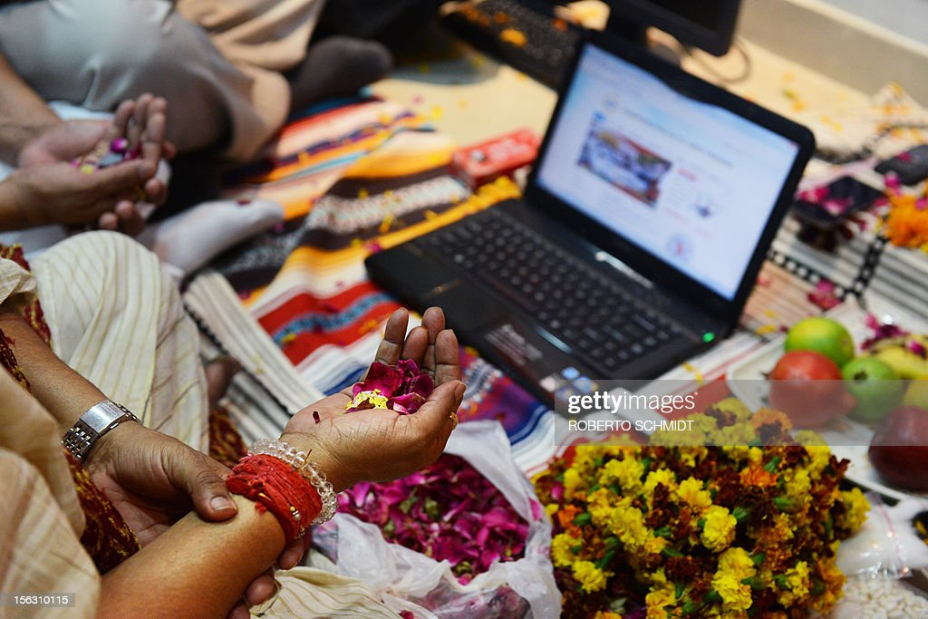 Indian traders hold flower petals as they worship electronic gadgets including iPads,laptops and mobile phones on Diwali, the Festival of Lights at their office in New Delhi on November 13, 2012. Since ages, the worshipping of account books has been an essential part of Diwali for the business community in India for prosperity of business. Signifying the modernisation of the retail trade in India, some traders are now including the worshipping of electronic gadgets. The festival of Diwali celebrates the victory of good over evil, light over darkness and knowledge over ignorance. AFP PHOTO/Roberto Schmidt