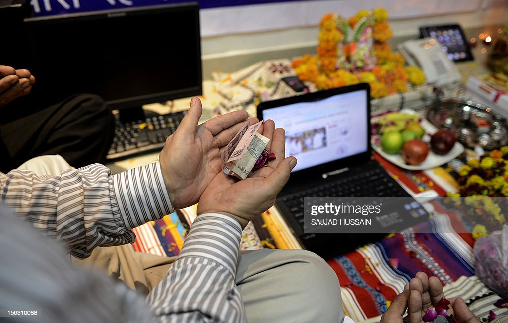 Indian traders hold money as they worship electronic gadgets including iPads,laptops and mobile phones on Diwali, the Festival of Lights at their office in New Delhi on November 13, 2012. Since ages, the worshipping of account books has been an essential part of Diwali for the business community in India for prosperity of business. Signifying the modernisation of the retail trade in India, some traders are now including the worshipping of electronic gadgets. The festival of Diwali celebrates the victory of good over evil, light over darkness and knowledge over ignorance. AFP PHOTO/SAJJAD HUSSAIN