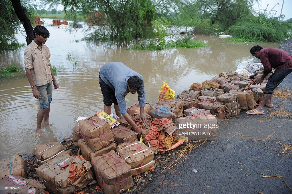 Indian traders shift wet and spoilt parcels containing 'kodiyas' or traditional oil lamps on the highway, on the outskirts of Ahmedabad on September 26, 2013. Majority of these kodiyas have been damaged owing to heavy rains and waterlogging in the godown where they were kept ready for sales for the forthcoming Navratri festivities. Gujarat state of Western India is in the grip of extreme weather and thousands of people have been evacuated in different regions across the state and the Indian Metrological Department (IMD) has warned of heavy rains in next 48 hours. AFP PHOTO / Sam PANTHAKY