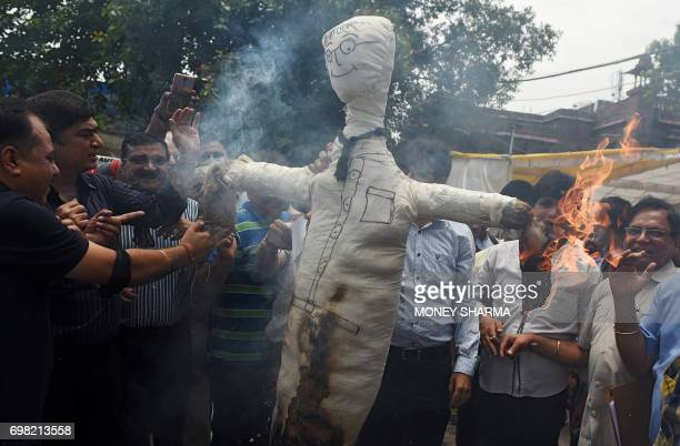 Indian traders shout slogans as they burn an effigy representing a tax worker during a protest against an upcoming new Goods and Services Tax rates...