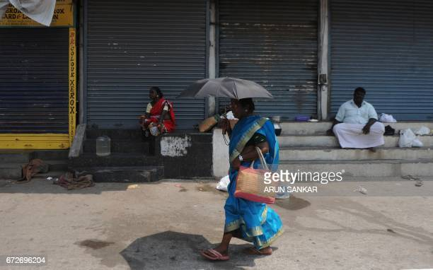 Indian traders sit next to shuttered stores during a statewide strike in support of farmers in Chennai on April 25 2017 Tamil Nadu state farmers are...
