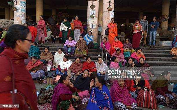 Indian traders wait outside a market to collect their materials after the building was damaged in a 67 magnitude earthquake in Imphal on January 4...