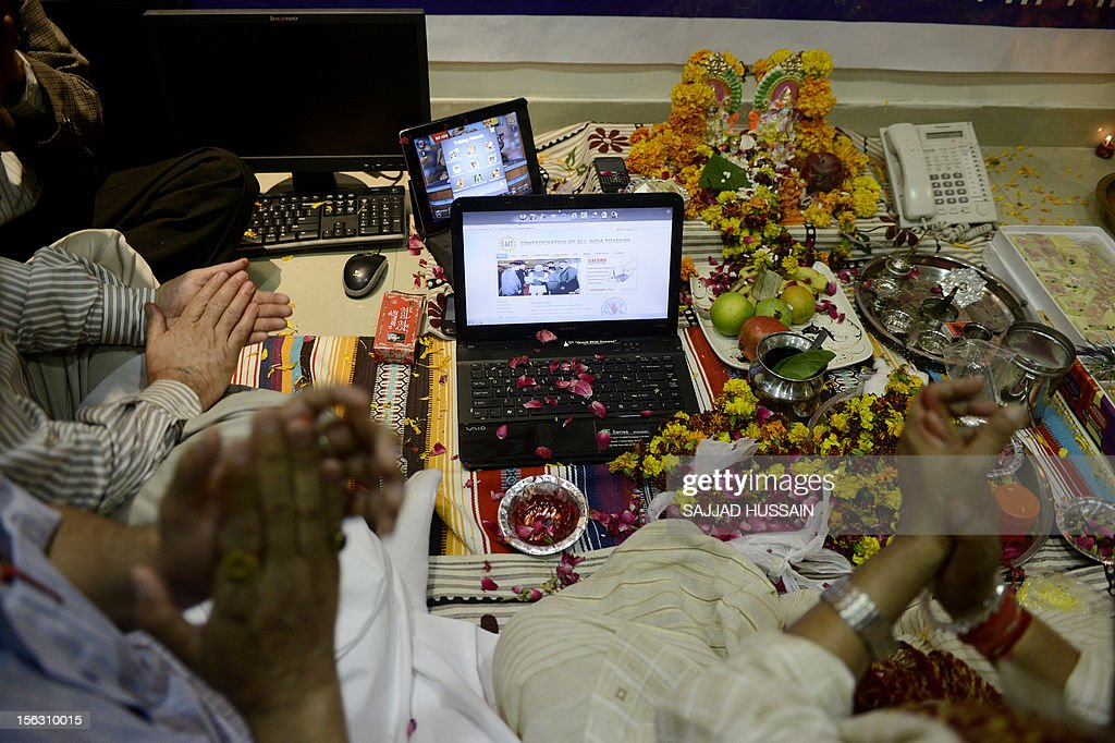 Indian traders worship electronic gadgets including i-Pads, laptops and mobile phones on Diwali, the Festival of Lights at their office in New Delhi on November 13, 2012. Since ages, the worshipping of account books has been an essential part of Diwali for the business community in India for prosperity of business. Signifying the modernisation of the retail trade in India, some traders are now including the worshipping of electronic gadgets. The festival of Diwali celebrates the victory of good over evil, light over darkness and knowledge over ignorance.