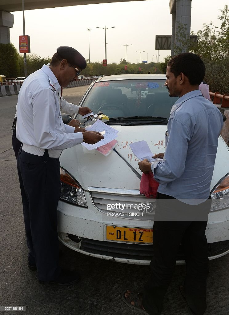 Indian traffic police personnel check the papers of the driver of a diesel taxi car in New Delhi on May 2, 2016. Hundreds of taxi drivers took to the streets of New Delhi to protest a court order banning diesel cabs from plying the roads of the world's most polluted capital. The ban would impact some 27,000 diesel taxis registered in Delhi, including app-based cab operators Ola and Uber. / AFP / PRAKASH