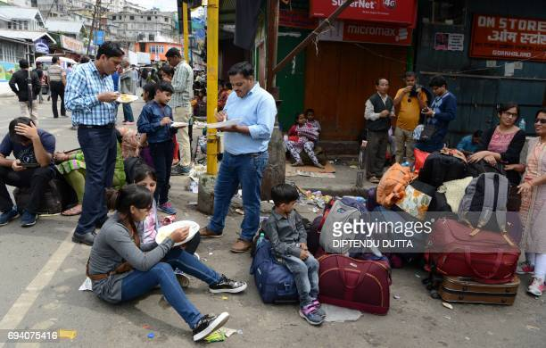 Indian travellers eat food distributed by locals as they wait for governmentprovided buses following clashes between police and protesters supporting...