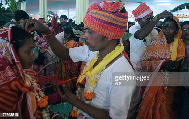 Indian tribal brides are anointed by their grooms as they take part in a mass marriage ceremony during a religious conference in Siliguri on February...