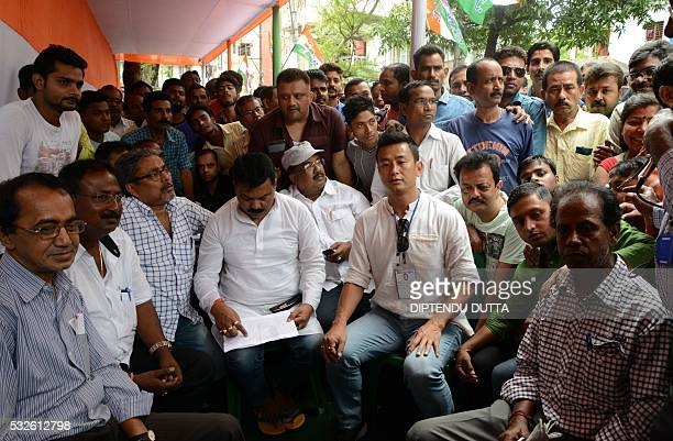 Indian Trinamool Congress party candidate and former footballer Baichung Bhutia watches a television set with supporters as he was defeated in the...