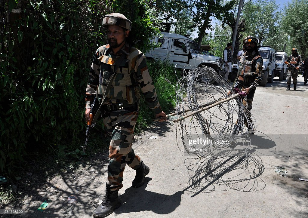 Indian troopers carrying barbed wires leave the from the debris of the residential house site in Khonshipora 25 miles west of srinagar on May 27,2016.Two rebels were killed by indian forces during a brief gunfight.