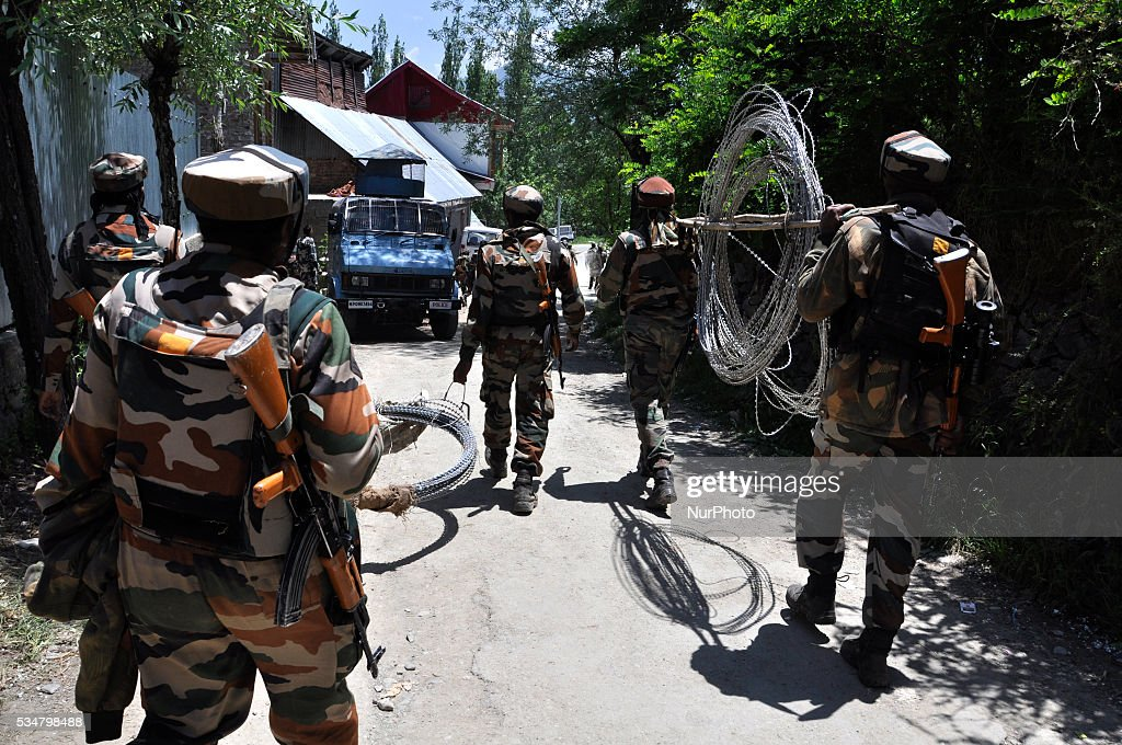 Indian troopers carrying barbed wires leave the gunbattle spot after after killing two suspected rebels site in Khonshipora 25 miles west of srinagar on May 27,2016.Two rebels were killed by indian forces during a brief gunfight