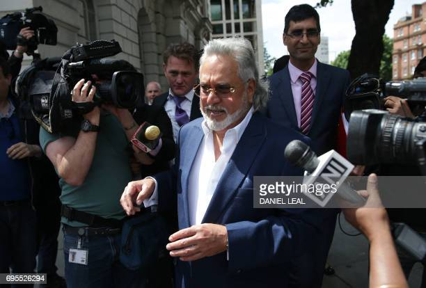 Indian tycoon Vijay Mallya is mobbed by members of the press as he leaves court in central London on June 13 2017 Mallya appeared in court to fight...