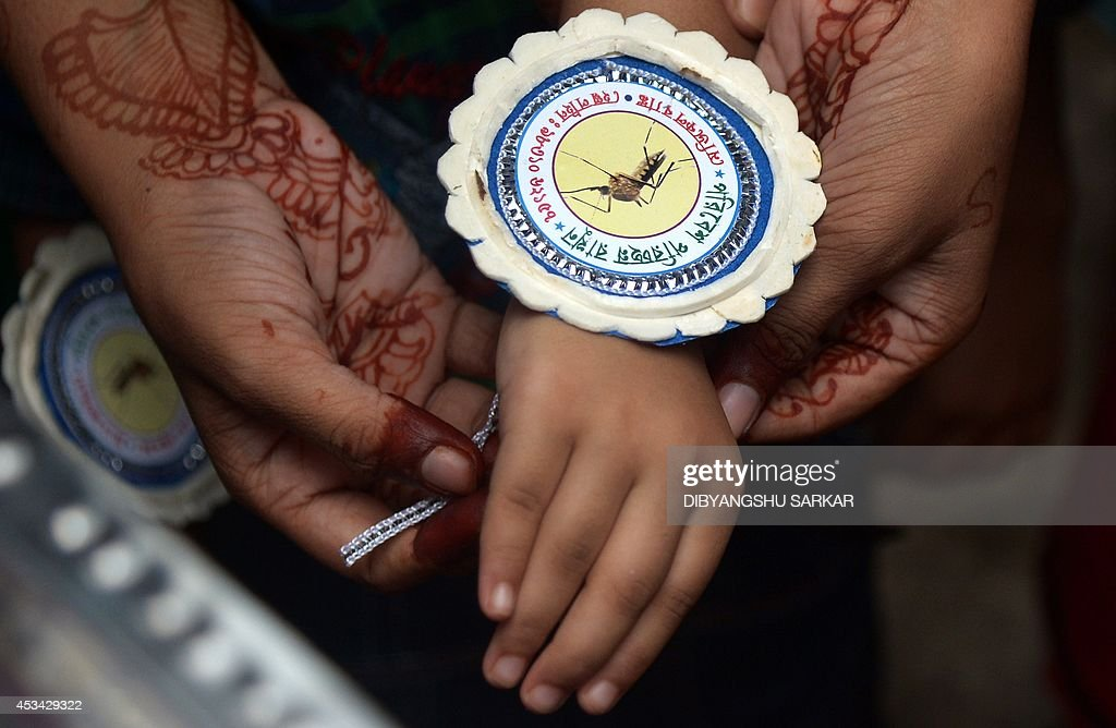 Indian under-priviledged girls tie 'rakhi' or sacred threads around the wrist of their brothers with a picture of a mosquito to create awareness of disease born by the insects, during the festival of Raksha Bandhan in Kolkata on August 10, 2014. An NGO organised the annual festival of Raksha Bandhan, which commemorates the abiding ties between siblings of opposite sex, is marked by a very simple ceremony in which a woman ties a rakhi, which may be a colourful thread, a simple bracelet, or a decorative string, around the wrist of her brother. AFP PHOTO/Dibyangshu SARKAR