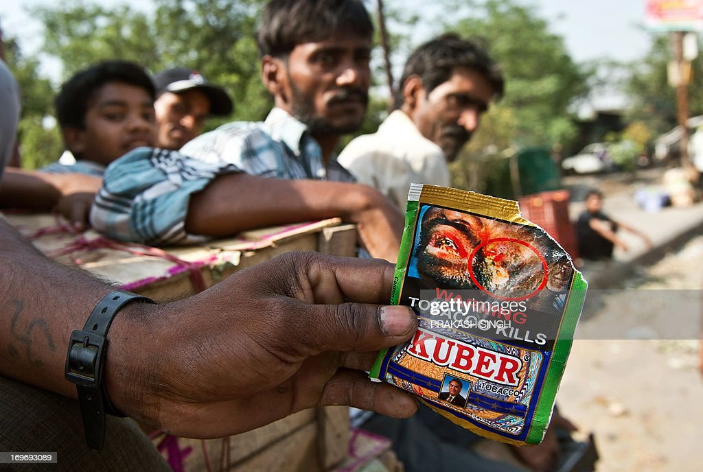A Indian vegetable vendor shows a packet of Chewing tobacco at a wholesale vegetable market in New Delhi on May 31, 2013. Observed around the world every year on May 31, World No Tobacco Day created by the World Health Organisation (WHO) this year has the theme 'Ban Tobacco Advertising, Promotion and Sponsorship'. AFP PHOTO/ Prakash SINGH
