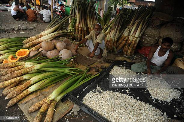 Indian vegetable vendors wait for customers as they sells arum root pumkin and garlic in Siliguri on July 16 2011 India's annual inflation...